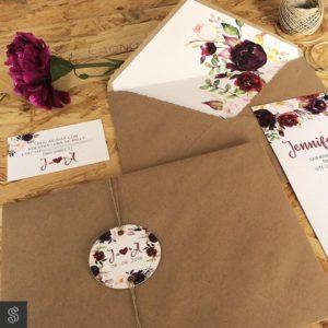 invitaciones con sobre kraft y forro decorativo y etiqueta circular en papel verjurado. La invitación y la tarjeta del número de cuenta también son en papel verjurado. El conjunto está decorado con motivos florales.