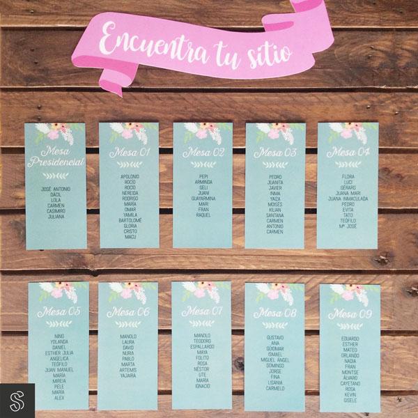 tarjetas de seating plan de boda colocadas en panel