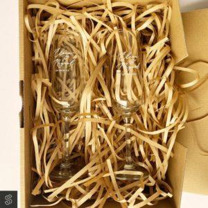 Copa Personalizada grabada con el nombre de los novios y la fecha presentada en caja kraft con relleno de viruta kraft